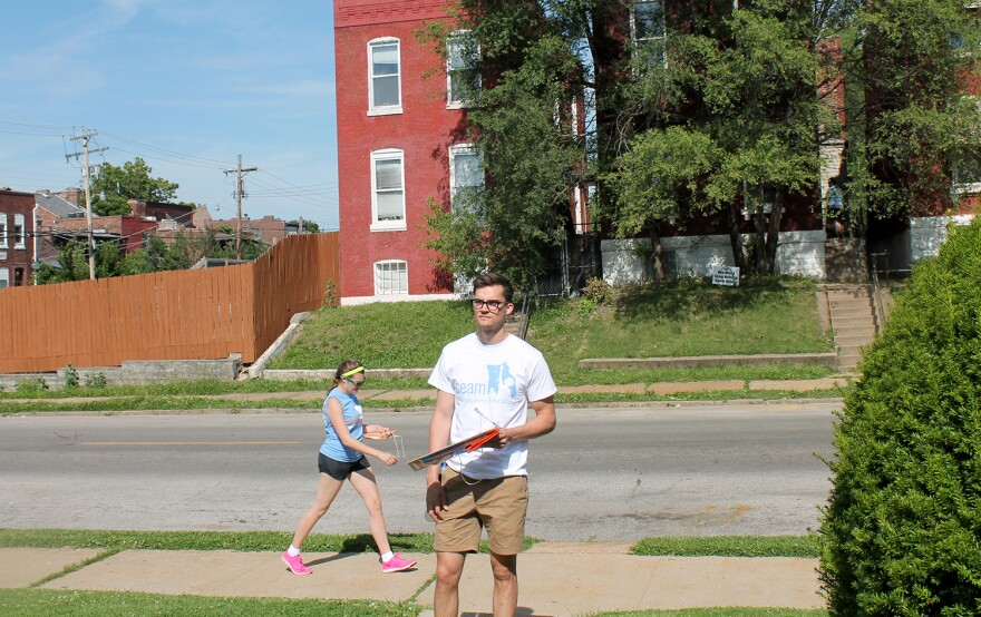 Jack Krewson waits on the sidewalk in the Dutchtown neighborhood while Gavin Schiffres knocks on a door June 8, 2017. Krewson and Schiffres want to open a school called Kairos in the area.