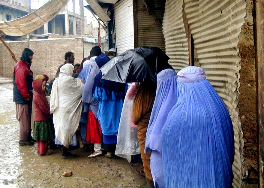 Afghan women wait in line to get bread at a World Food Program-run bakery in Kabul, Afghanistan, in December 2000. The World Food Program provided subsidized bread to about a fifth of the city's population during the Taliban era, from 1996 to 2001.