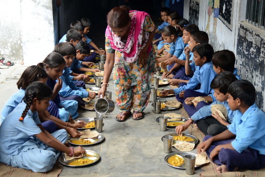 Indian schoolchildren eat their free midday meal.