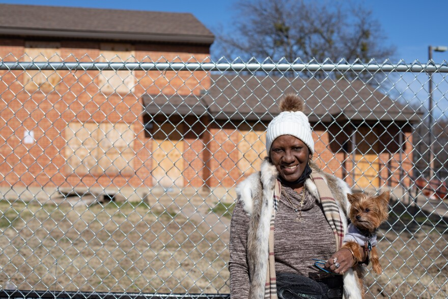 Carolyn Tubbs stands in front of a chain link fence, holding a little fuzzy dog in a sweater. Behind her is her old apartment, in a red brick building that has been boarded up.