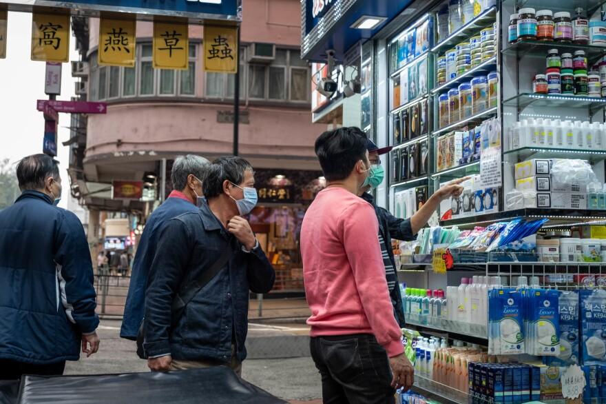 People inspect surgical masks for sale. Hong Kong health authorities have encouraged people to wear masks to control the spread of the novel coronavirus. Some stores have increased the price because of demand.