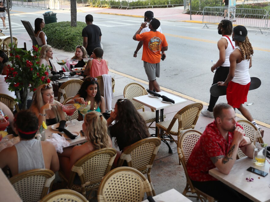 As late as March 17, people eat at a restaurant along Ocean Drive in Miami Beach, Fla., several days after President Trump declared a national emergency.