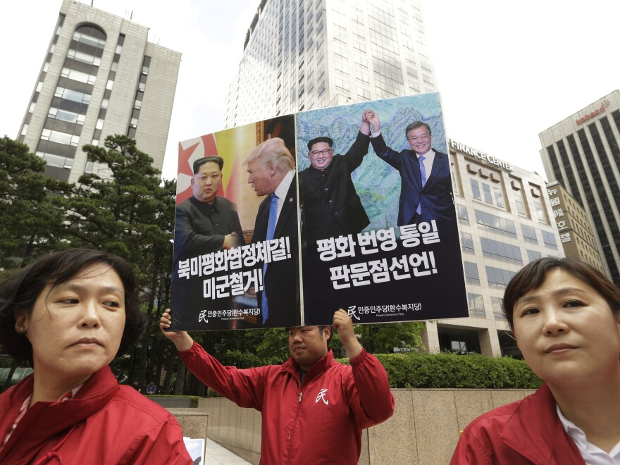 "An activist holds up a banner showing photos of President Trump, North Korean leader Kim Jong Un and South Korean President Moon Jae-in, during a rally for peace at the Singapore Embassy in Seoul on Tuesday. The signs read: ""Peace treaty."""