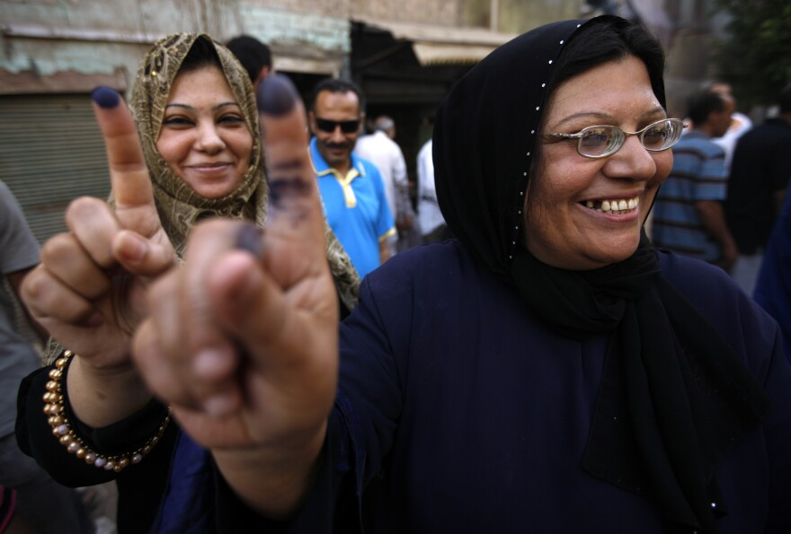Two women show their inked fingers after casting their votes on the first day of the Presidential election at a polling center in Old Cairo, Egypt, on Wednesday.