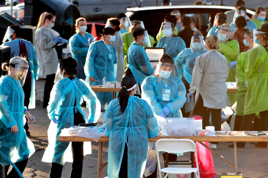 Medical personnel prepare to test hundreds of people for the coronavirus. They lined up in vehicles last week in a Phoenix neighborhood.