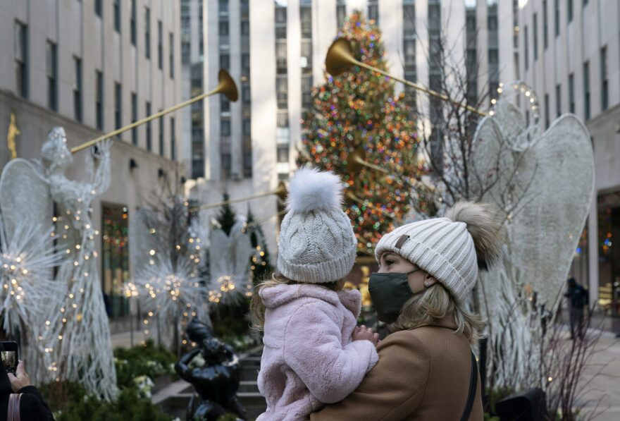 A woman holds her daughter as they look at the Rockefeller Center Christmas Tree, Thursday, Dec. 3, 2020 in New York.  What's normally a chaotic, crowded tourist hotspot during the holiday season is instead a mask-mandated, time-limited, socially distanced locale due to the coronavirus pandemic.  (Mark Lennihan/AP)