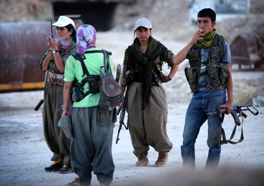 Three female members of Turkey's Kurdistan Workers' Party (PKK) and an Iraqi Kurdish peshmerga fighter stand near the front line in Makhmur, in northern Iraq, on Aug. 9. The Turkish and Iraqi Kurds have been fighting together against the Islamic State.