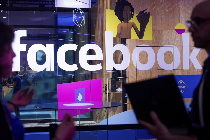 In this April 18, 2017 photo, conference workers speak in front of a demo booth at Facebook's annual F8 developer conference in San Jose, Calif.  (Noah Berger/AP)