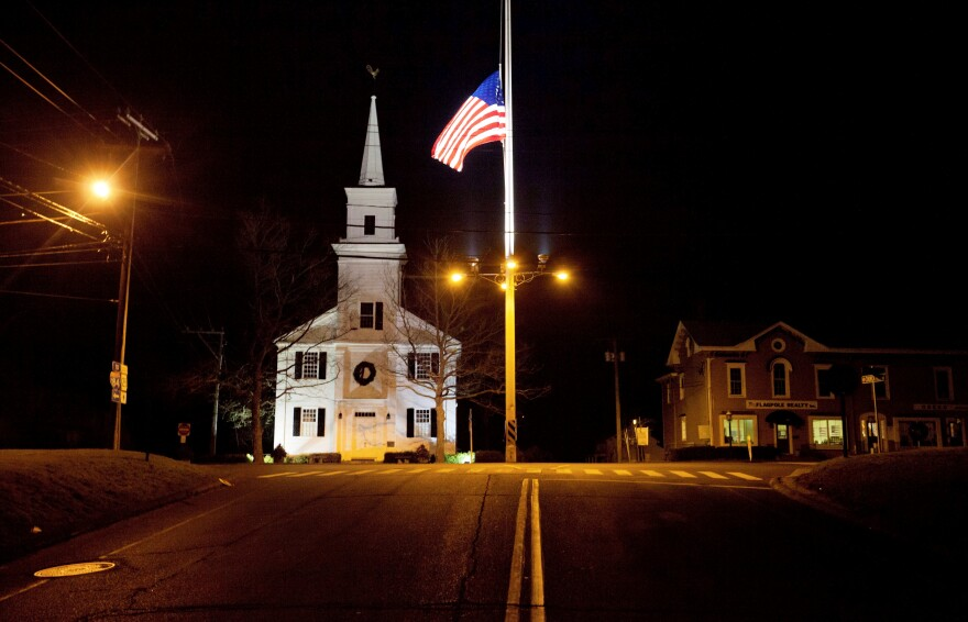 A U.S. flag flies at half staff on Main Street in Newtown, Conn., on Dec. 15, 2012, in honor of the 26 students and staff killed in a shooting at Sandy Hook Elementary School.