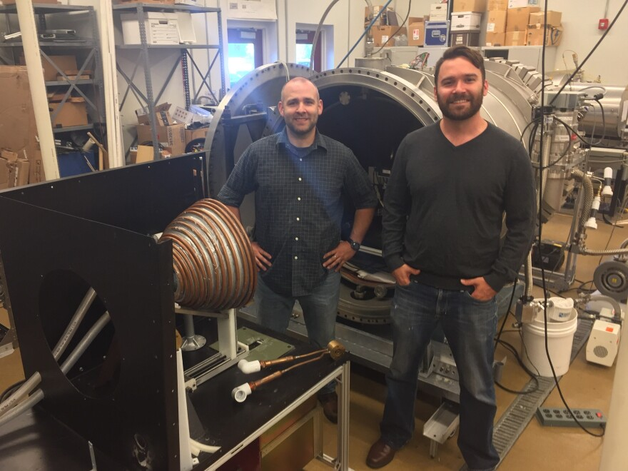 Colorado School of Mines Space Resources graduate researchers Curtis Purrington (left) and Hunter Williams stand next to experimental lab equipment in Golden, Colo.