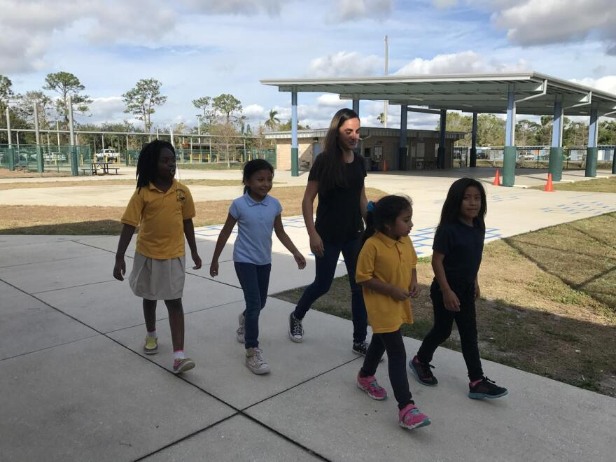 Emily Deleon, 14, walking elementary school kids to the playground during recess before she tutors them in the classroom.