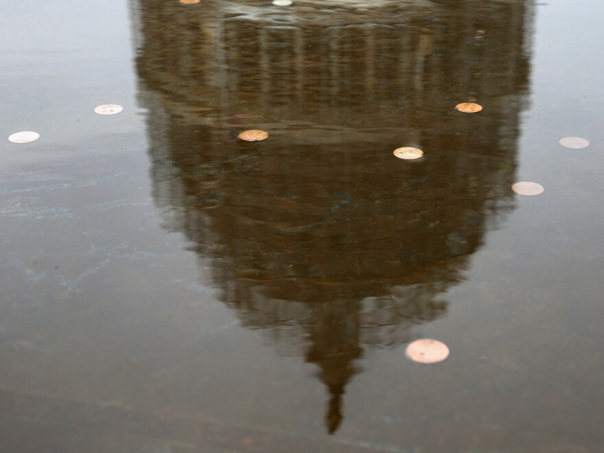 The amount of money spent on Capitol Hill is way more than small change — but the impact of that money is a little murky. Here, the U.S. Capitol is reflected in a fountain full of coins on Election Day this year.