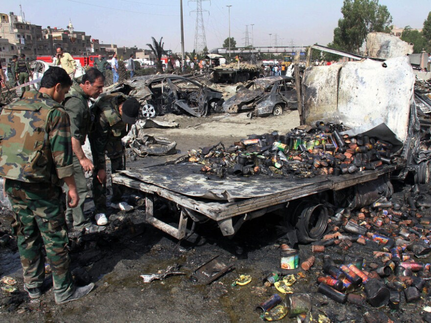 Syrian soldiers check a burned truck in front of a damaged military intelligence building where two bombs exploded, at Qazaz neighborhood in the Syrian capital, Damascus, on Thursday.