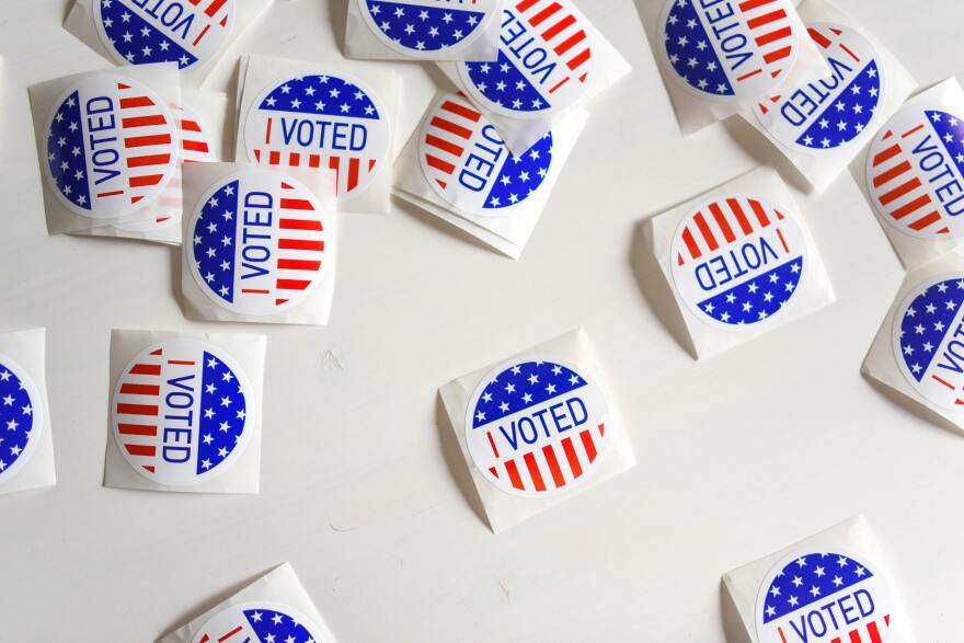 """I voted stickers are scattered on a white background. The stickers are circles. The top is blue and covered in stars. The bottom is red and white stripes. The middle says """"I voted."""""""
