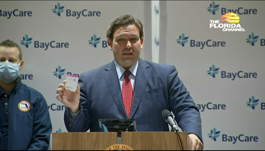 Gov. DeSantis holds up a rapid testing kit during a press conference at Morton Plant Hospital in Clearwater Tuesday