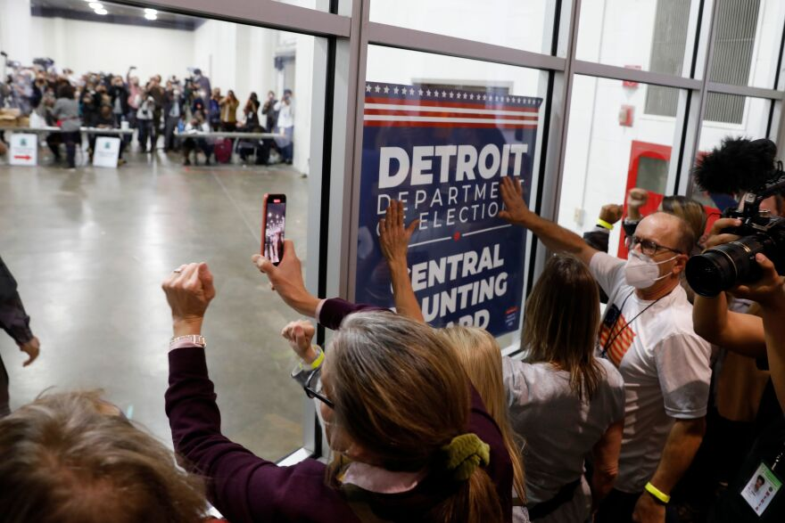 Supporters of President Trump bang on the glass and chant slogans outside the room where absentee ballots for the 2020 general election were counted at TCF Center on November 4, in Detroit, Mich.