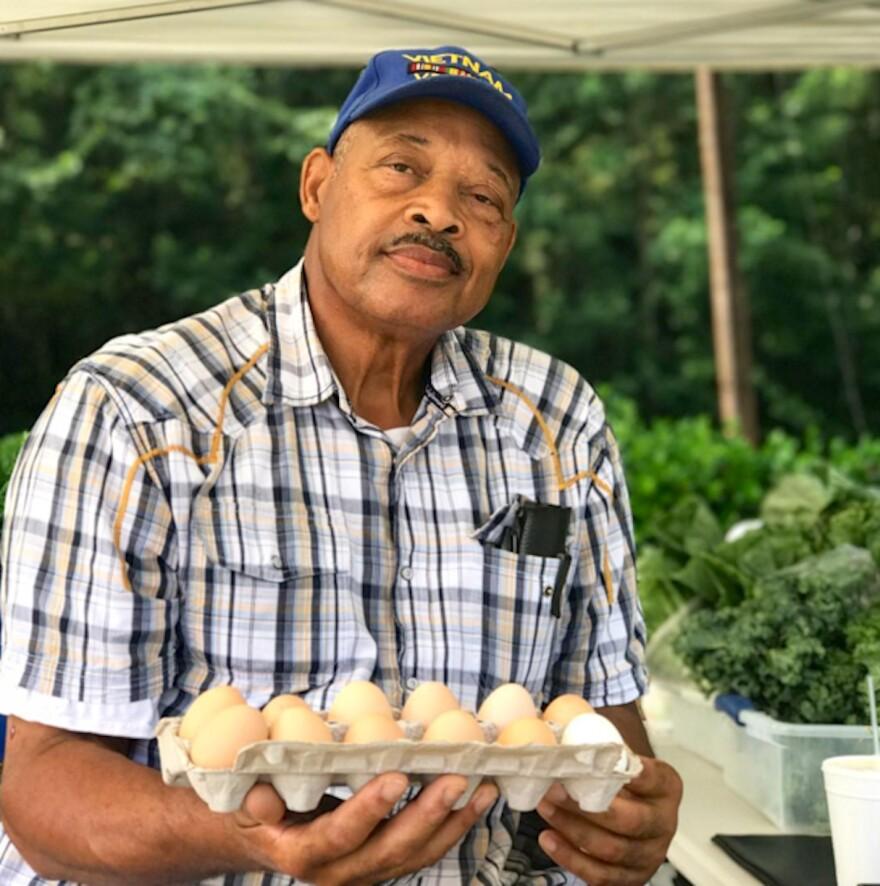 Paul Brewington, farmer, holding a dozen eggs.