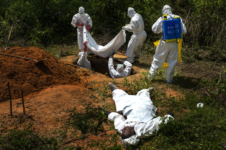 Alexander Morris lies flat on his back after he fainted due to the extreme heat inside a protective suit, while the Lofa County Health Department team buries his sister, on Nov. 7 in Voinjama, Liberia.