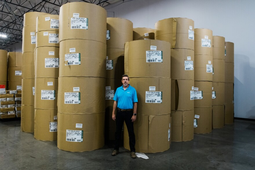 Jeff Ellington, president and COO of Runbeck Election Services, stands in front of massive rolls of paper used to create mail-in ballots.