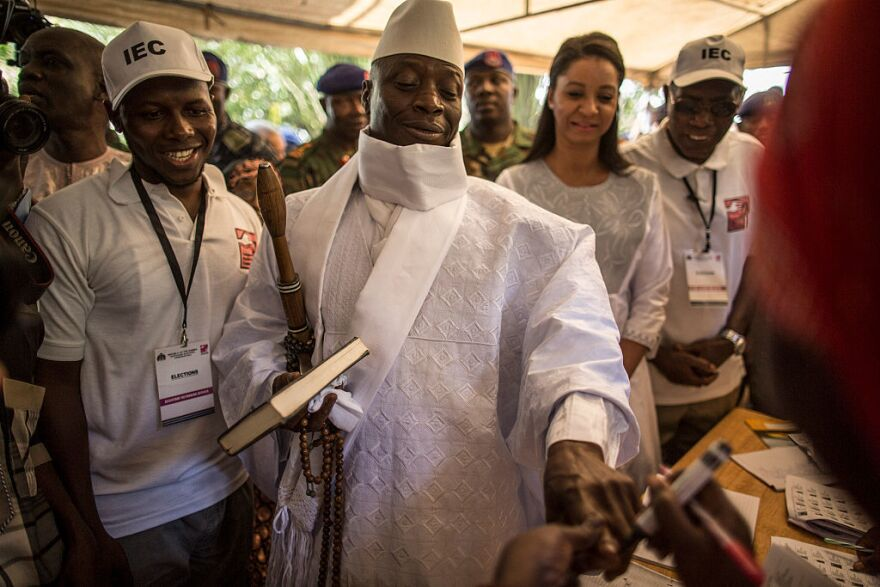 Incumbent Gambian President Yahya Jammeh (center) has his finger inked before casting his marble in a polling station during the presidential election.
