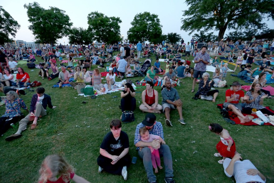 A crowd sits on the lawn during Rock the Park by Mueller Lake.