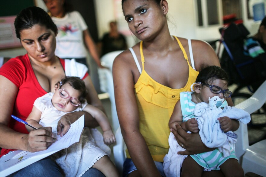 Infants born with microcephaly are held by mothers at a meeting for mothers of children with special needs in Recife, Brazil.