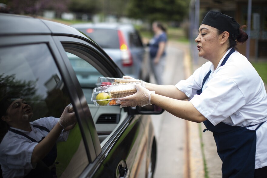 Austin ISD employee Rosa Montalvo hands lunch to parents parked outside Dawson Elementary School. The district has been offering meals while schools are closed.