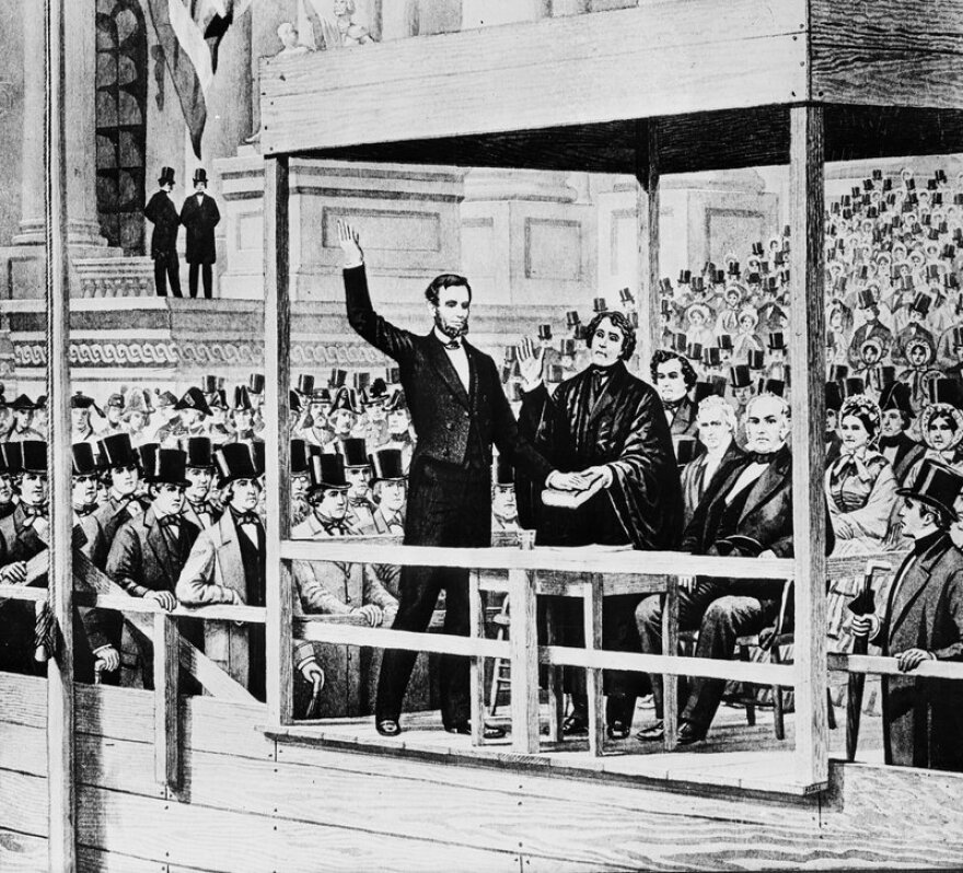 Black and white image of Abraham Lincoln standing before a crowd of people, taking the presidential oath with his hand on a Bible.
