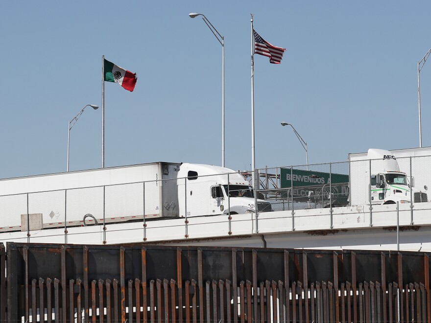 Trucks are seen heading into the United States from Mexico along the Bridge of the Americas in El Paso, Texas, on Tuesday. U.S. industries say President Trump's threatened tariffs on goods from Mexico raised uncertainty just as they were looking forward to a new trade agreement.