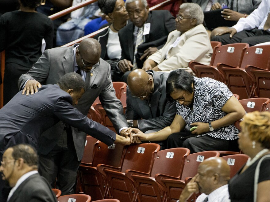Mourners pray before the funeral service for the Rev. Clementa Pinckney in Charleston, S.C.