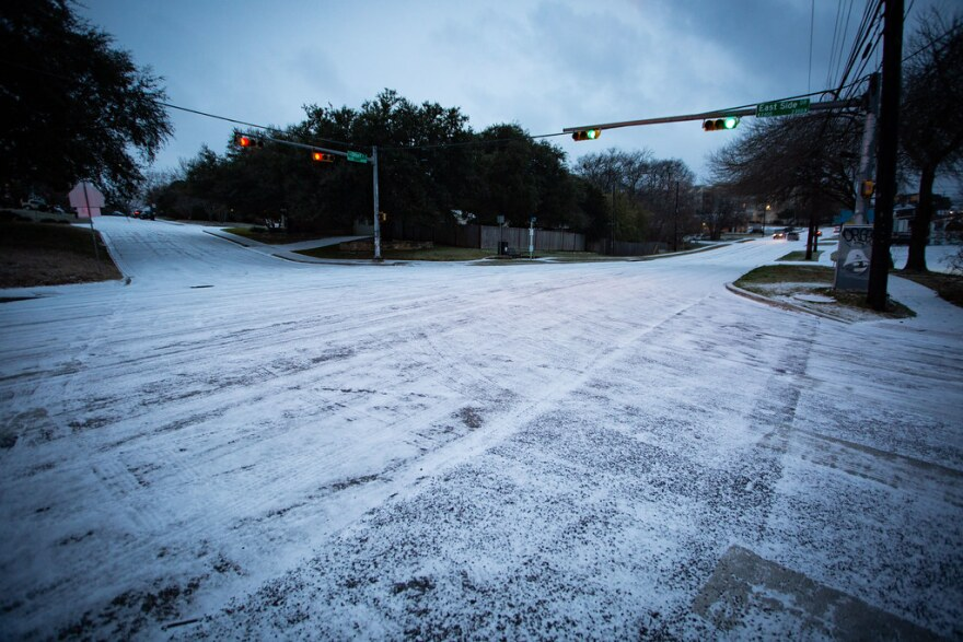 Ice and snow accumulate on the road at an intersection in the Travis Heights neighborhood of South Austin during a winter storm Sunday.