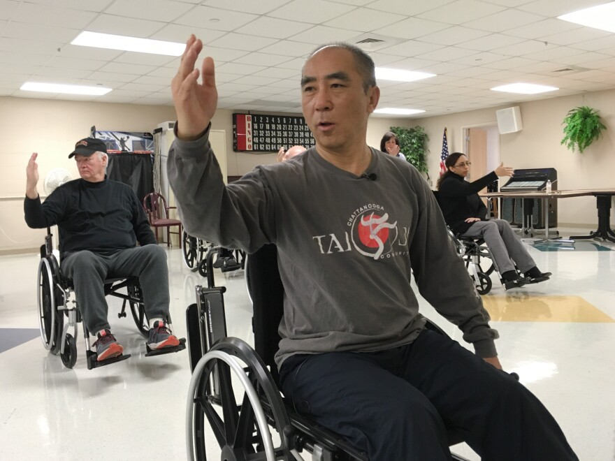 Medical anthropologist Zibin Guo (center) adapted tai chi for people with limited mobility. Though there's little research evidence confirming that tai chi eases drug cravings or symptoms of post-traumatic stress, the veterans in Guo's class say the program helps them.