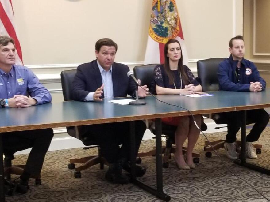 Gov. Ron Desantis at a table with members of his staff.