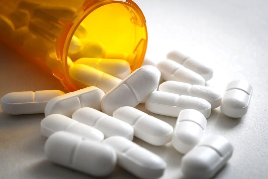 Photo of white pills spilling out of an orange prescription bottle.