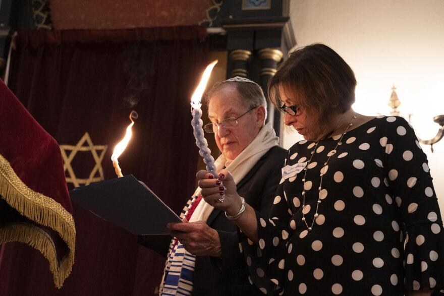 B'nai Sholom President Michael Bukstein and Joni Reisler Abramowitz light the ceremonial havdalah candles during a deconsecration ceremony at the temple on May 18, 2019.
