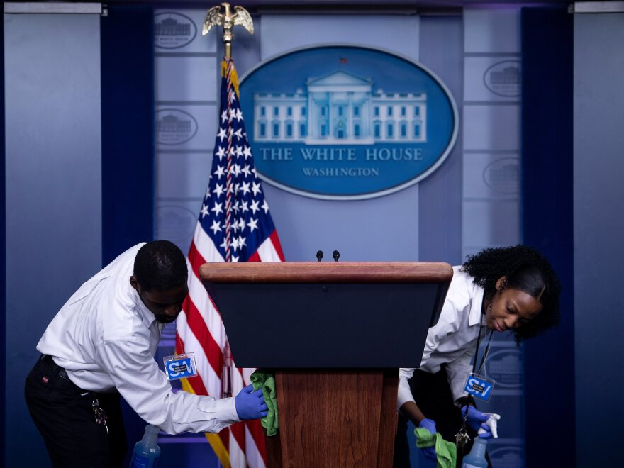 Cleaners sanitize the lectern in the White House briefing room after a coronavirus briefing on March 16, the day Trump announced his 15-day guidelines.
