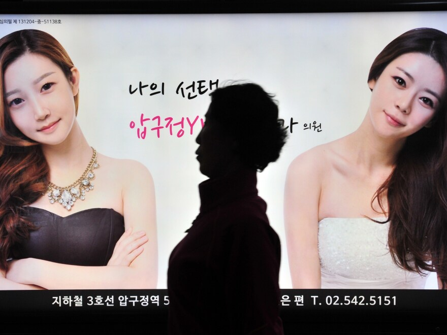 A pedestrian walks past an ad for a cosmetic surgery clinic at a subway station in Seoul in 2014. Such ads were later restricted after complaints that they were fueling an unhealthy obsession with body image.