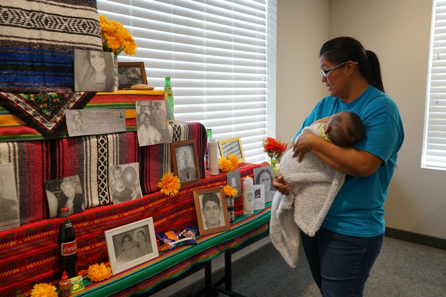 Mother holds baby and looks at colorful altar.
