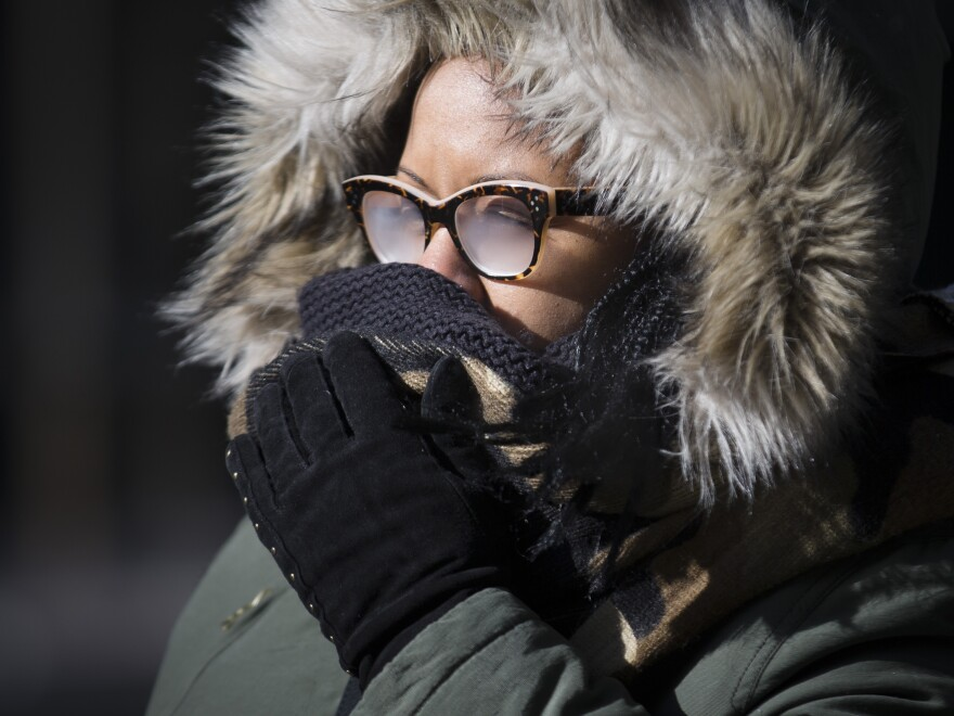 Pedestrians brave the cold during their morning commute on Friday in New York. Arctic air and bitterly cold wind is moving across the Northeast, plunging temperatures into record-low single digits, accompanied by subzero wind chills.