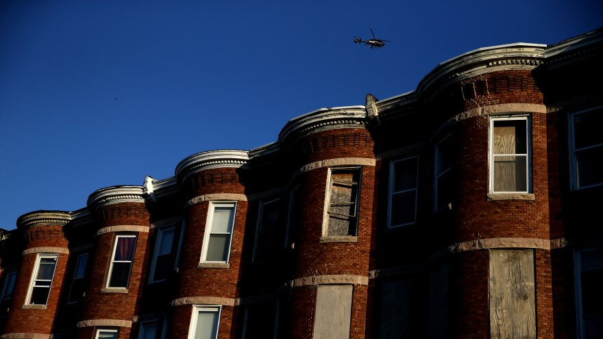 """A helicopter flies over a section of Baltimore affected by riots. Richard Rothstein writes that recent unrest in Baltimore is the legacy of a century of federal, state and local policies designed to """"quarantine Baltimore's black population in isolated slums."""""""