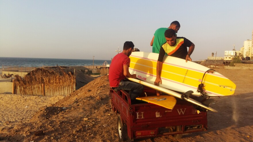 Members of the Gaza Surf Club drive a tuk-tuk down to the beach, to carry their surfboards.