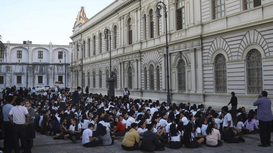 Students sit in an open area after their school was evacuated in Veracruz, Mexico, on Friday, after a magnitude 7.2 earthquake. Later Friday, 13 people died after a helicopter surveying the damage near the epicenter crashed.