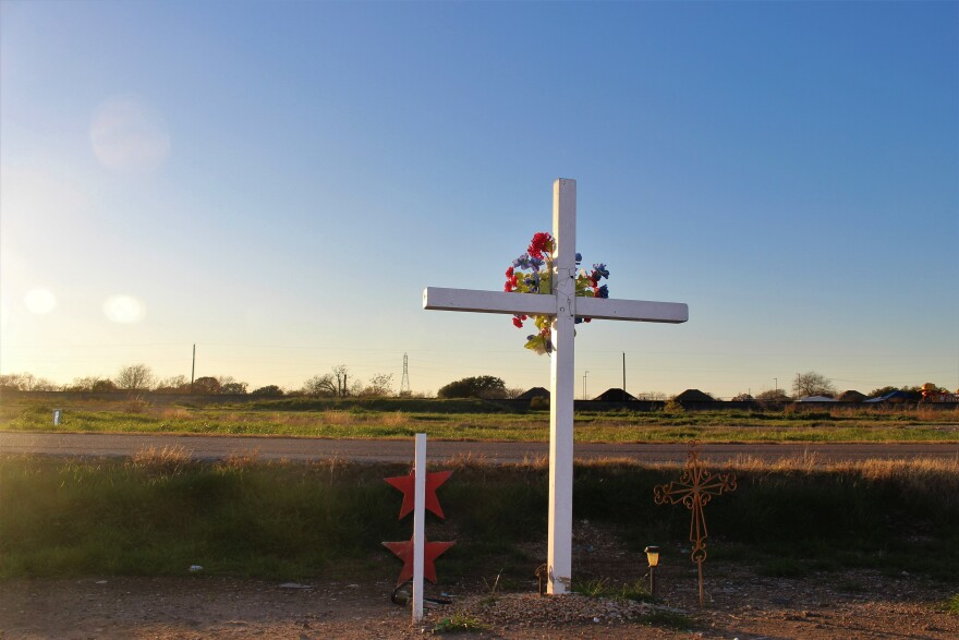 Eight years after the explosion, residents still maintain a fresh wreath of flowers on a white cross, just across the street from the former site of the West Fertilizer Company.