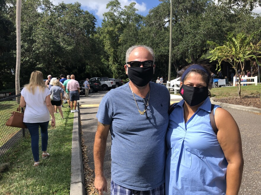 Herb and Maria Valdez wearing masks standing outside the Riverview Branch Library to vote early.