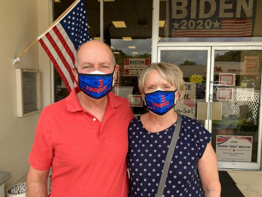 """A man in a red shirt and a Blue """"Biden-Harris"""" face mask has his arm around a woman in a blue, polka-dot shirt wearing a similar mask."""