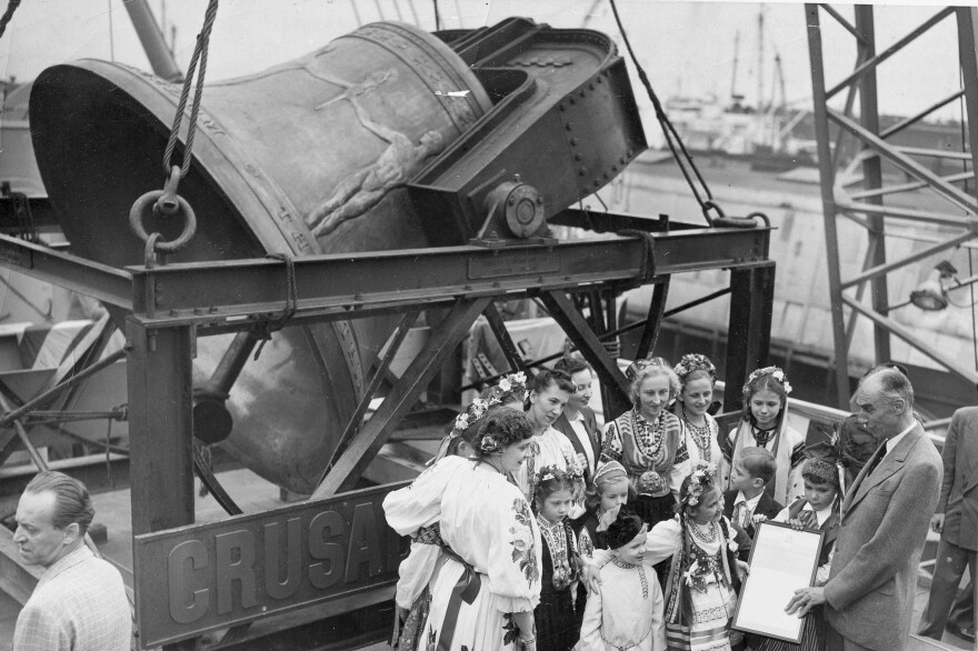 A group of former displaced persons helps to load the Freedom Bell aboard a Navy transport vessel in Brooklyn, New York, Oct. 9, 1950. One of the children, Eva Zandler, 8, originally from Poland, presents a scroll to be enshrined in the Freedom Bell Tower in Berlin, to Frederick Osborn, New York City chairman for the Crusade for Freedom.