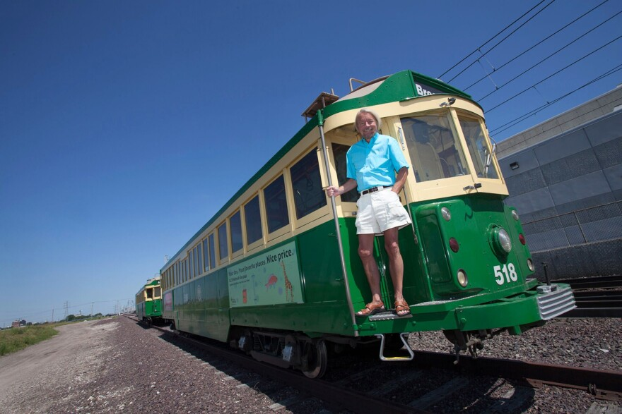 Joe Edwards poses with a green and white trolley car purchased in Seattle for the Loop Trolley.