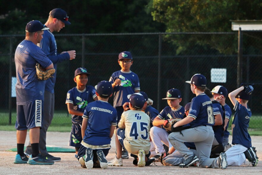 Youth baseball players take a knee on the field