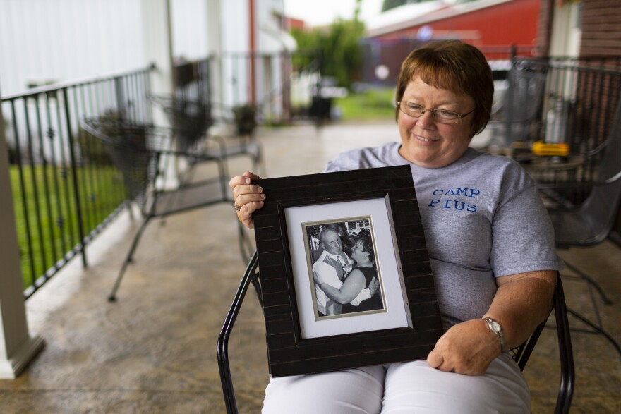 "Lisa Hobbs holds a picture of her husband, Gene ""Pius"" Hobbs. Hobbs was raking gravel with the Meade County public works crew when a dump truck backed over and killed him."