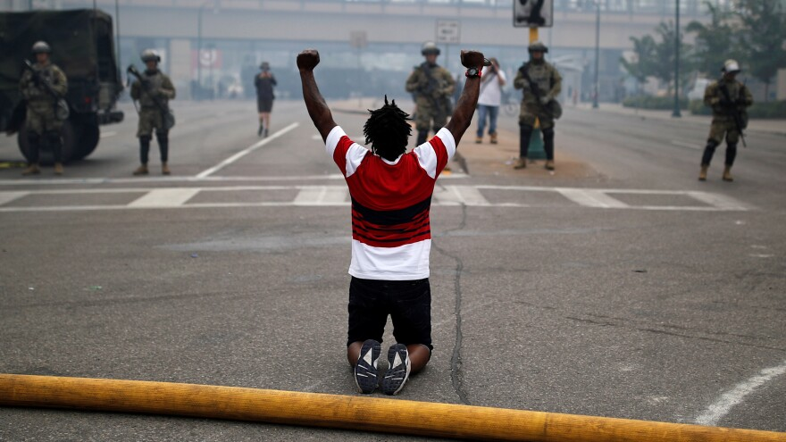 A man kneels as he confronts National Guard members guarding the area in the aftermath of a protest in Minneapolis.